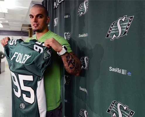 DL Ricky Foley poses for a photo with his new #95 Green and White Roughriders jersey.
