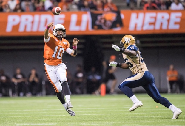 BC Lions' quarterback Jonathon Jennings, left, throws downfield under pressure during the first half of a CFL football game in Vancouver, B.C., on Saturday, October 10, 2015. THE CANADIAN PRESS/Jimmy Jeong