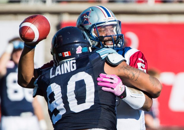 Montreal Alouettes quarterback Anthony Boone, right, is sacked by Toronto Argonauts' Cleyon Laing during second half CFL football action in Montreal, Monday, October 12, 2015. THE CANADIAN PRESS/Graham Hughes