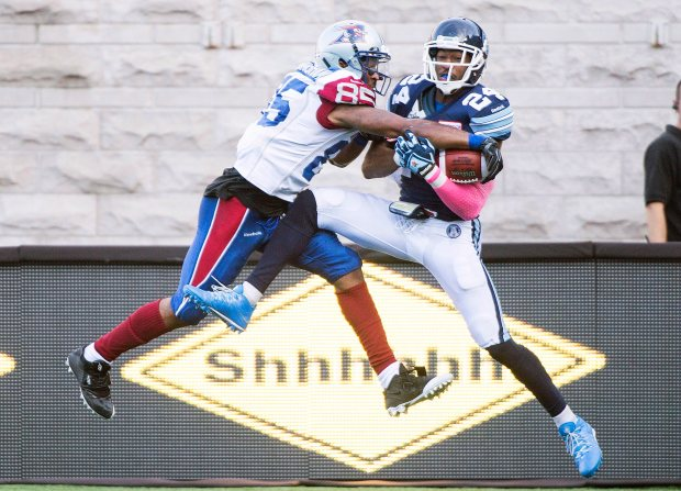 Montreal Alouettes' B.J. Cunningham, left, challenges Toronto Argonauts' A.J. Jefferson during second half CFL football action in Montreal, Monday, October 12, 2015. THE CANADIAN PRESS/Graham Hughes